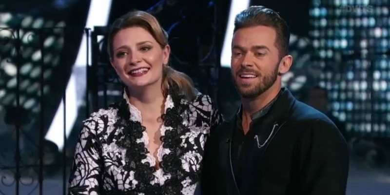 Mischa Barton and Artem Chigvintsev are smiling as they listen to the judges.