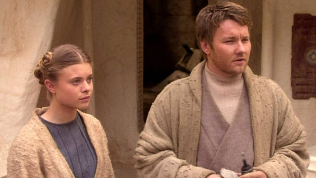 Beru and Lars wearing modest tan robes, looking off to the right of the frame bemusedly