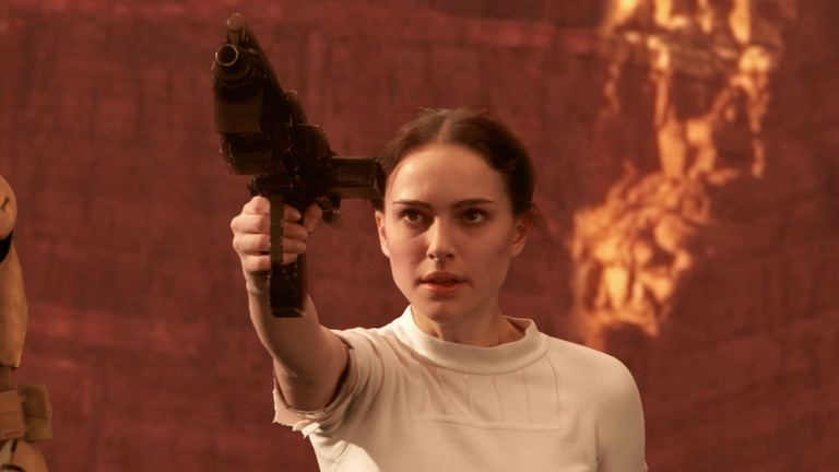 Natalie Portman as Padme, wearing a white shirt and aiming a gun off into the distance