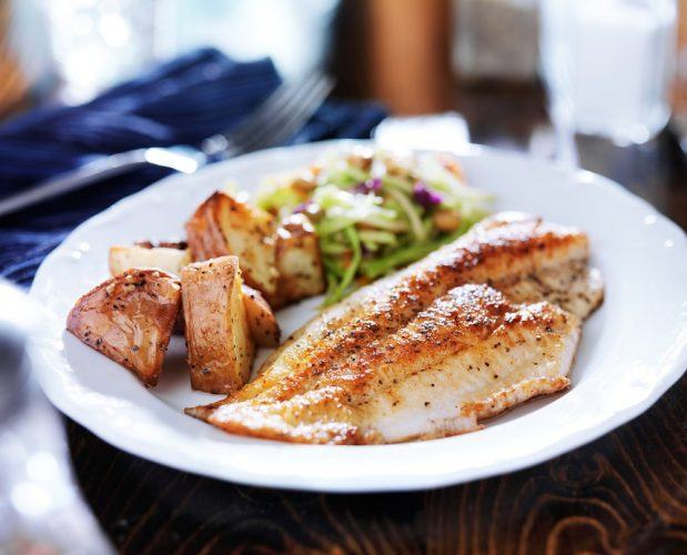 fish with potatoes and salad on a plate