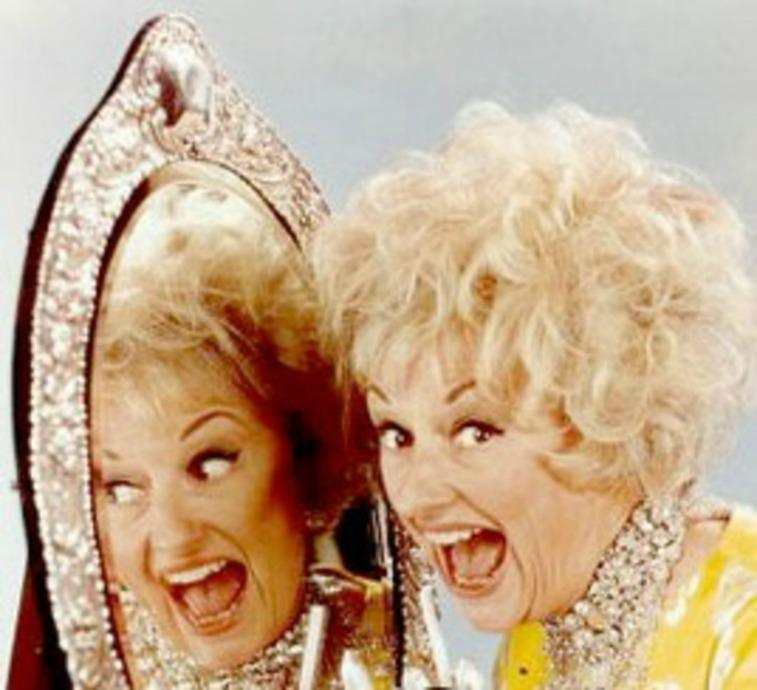 Phyllis Diller smiling with her mouth open wide next to a mirror where you can see her reflection