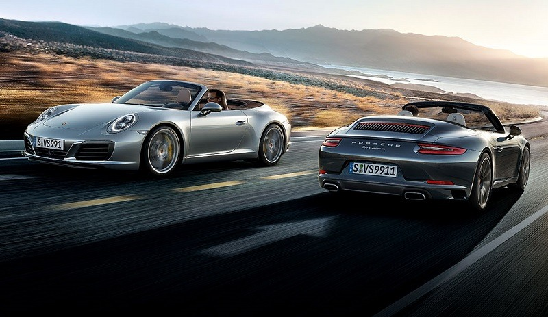 Two Porsche Carrera 911 models passing each other on a coastal highway
