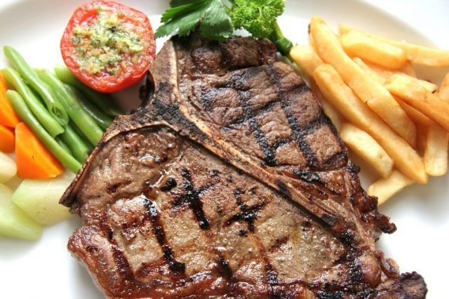 T-bone steak with a tomato, veggies, and fries