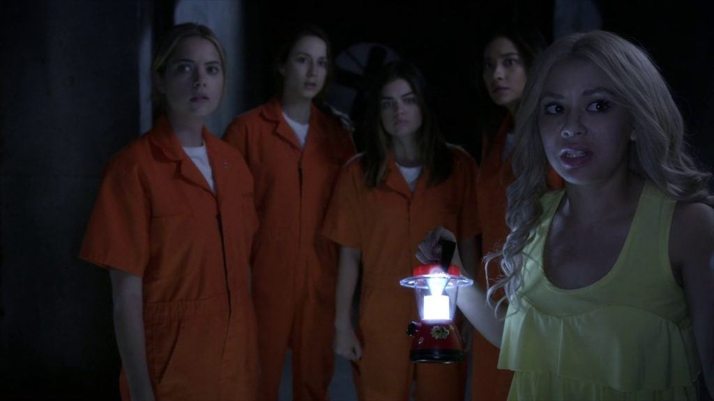 Four girls in orange jumpsuits stand behind a girl holding a lantern