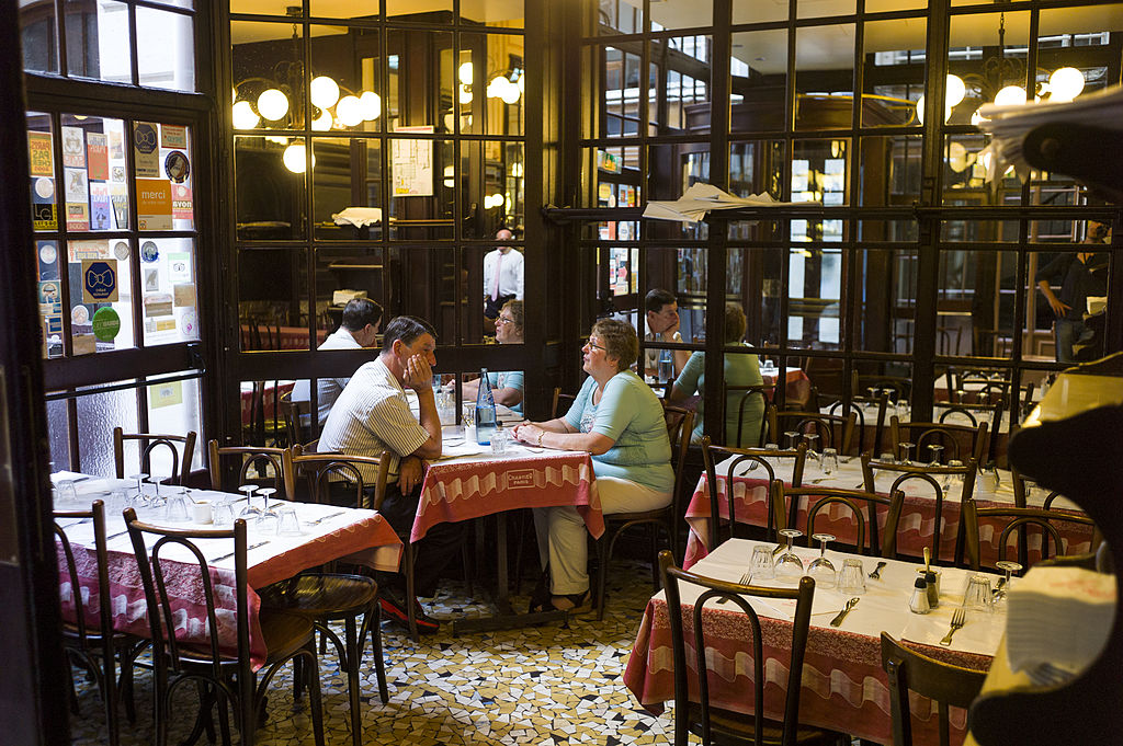 a couple waits in a french brasserie
