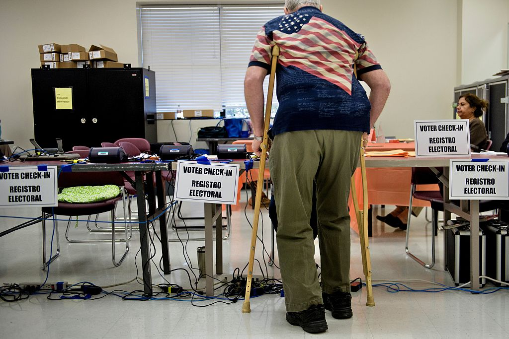 A senior, who likely cares about retirement issues, checks in at an early voting center.