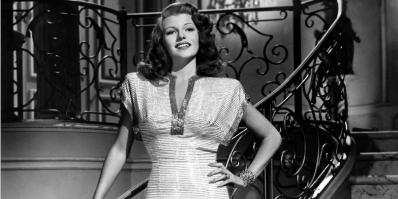 Rita Hayworth is posing on a staircase in a dress and one hand on her hip.