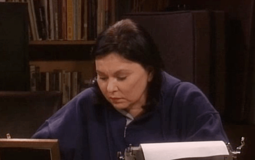Roseanne sits at her desk with a typewriter