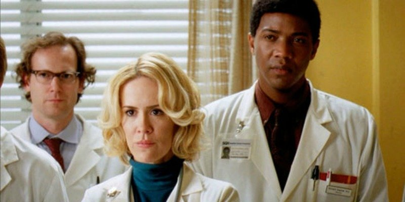 Sarah Paulson is dressed as a doctor along with two other people.