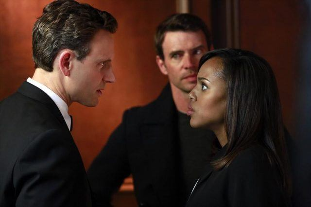 Fitz stares at Olivia as Jake looks at him in the background.