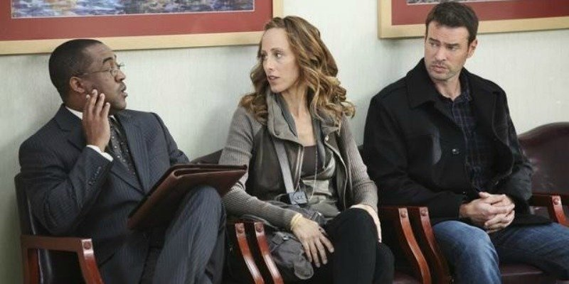 Scott Foley's character along with two other characters are sitting next to each other talking in a waiting room.