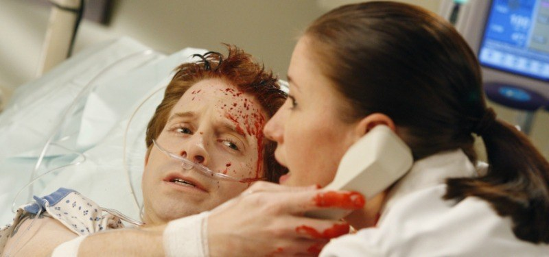 Seth Green is covered in blood in a hospital bed and is holding up a phone to a doctor's ear.