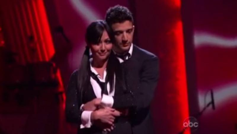 Shannen Dohert is dressed as a school girl and is being hugged by Mark Ballas.