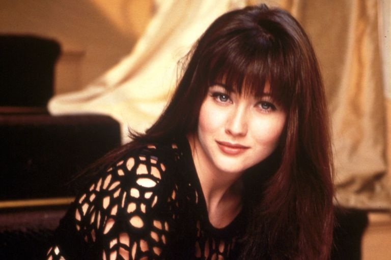 A young Shannen Doherty, wearing a black lace top and smiling