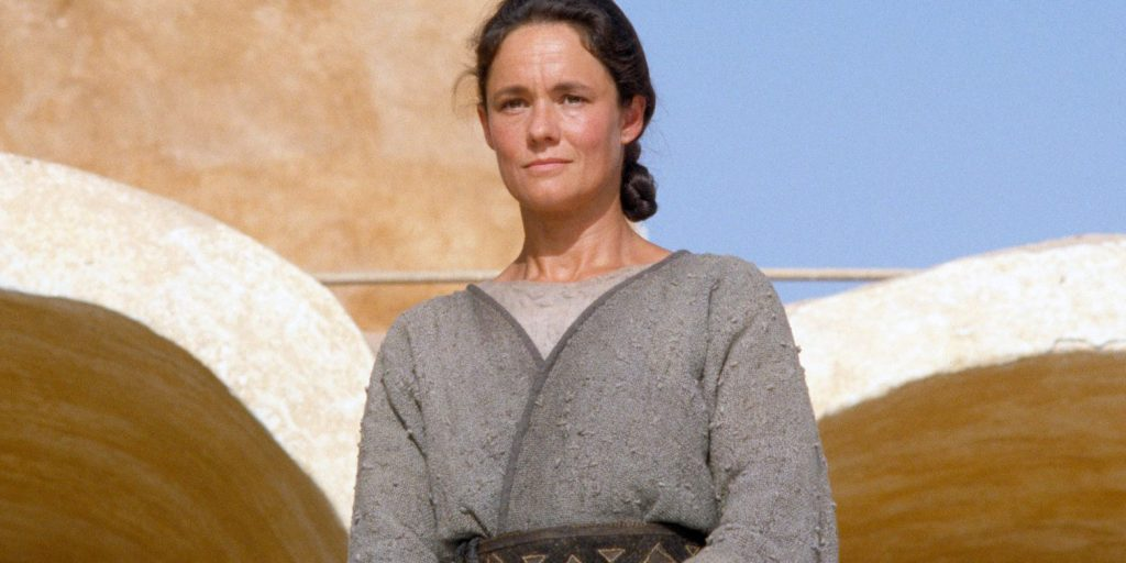 Shmie Skywalker, wearing a modest tan tunic, looking off into the distance with concern