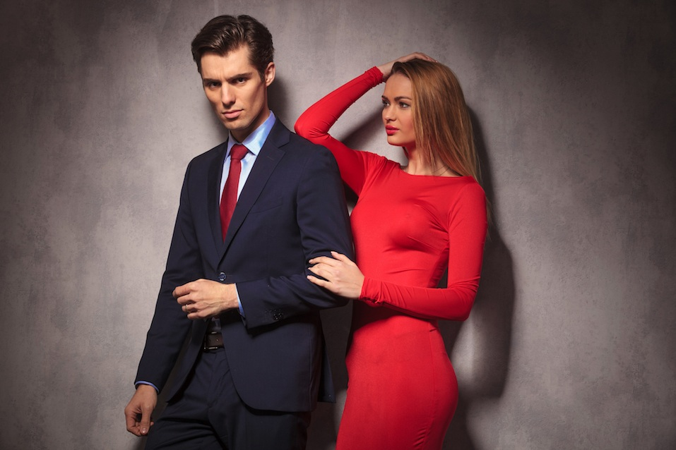 woman in red dress looking at her lover in suit and tie