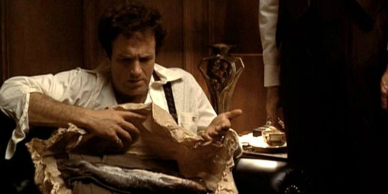 Sonny looks down at a fish wrapped in paper in The Godfather.