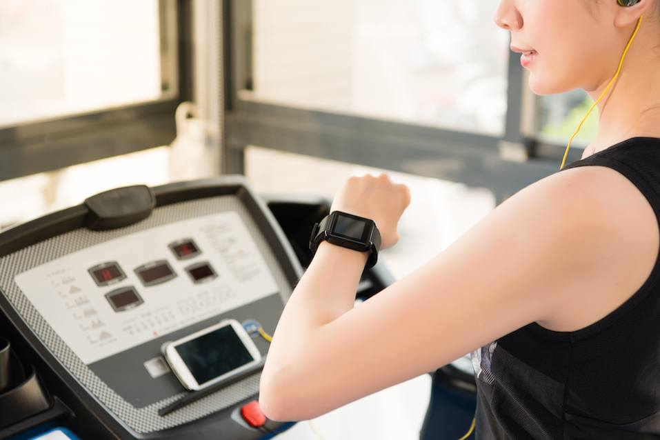 sport asian woman use smartwatch check pulse rate listening