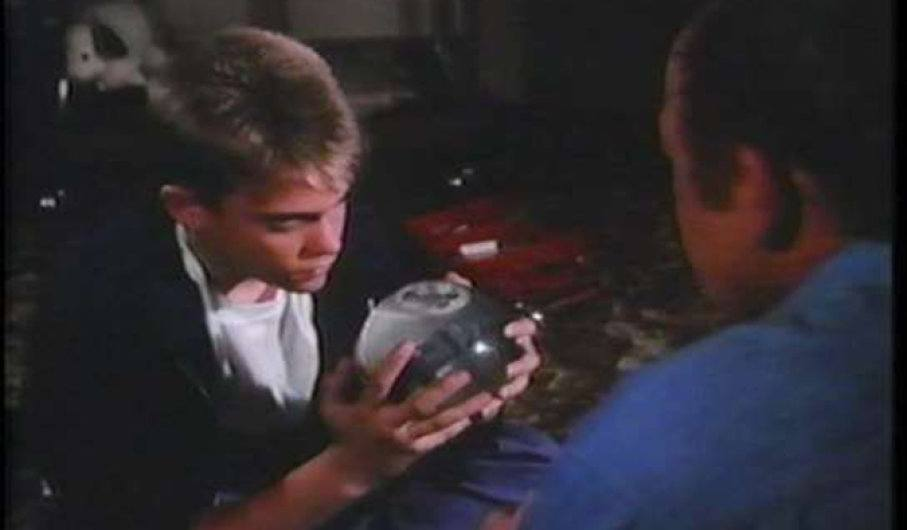 Tommy Westphall staring at snow globe as his father holds it