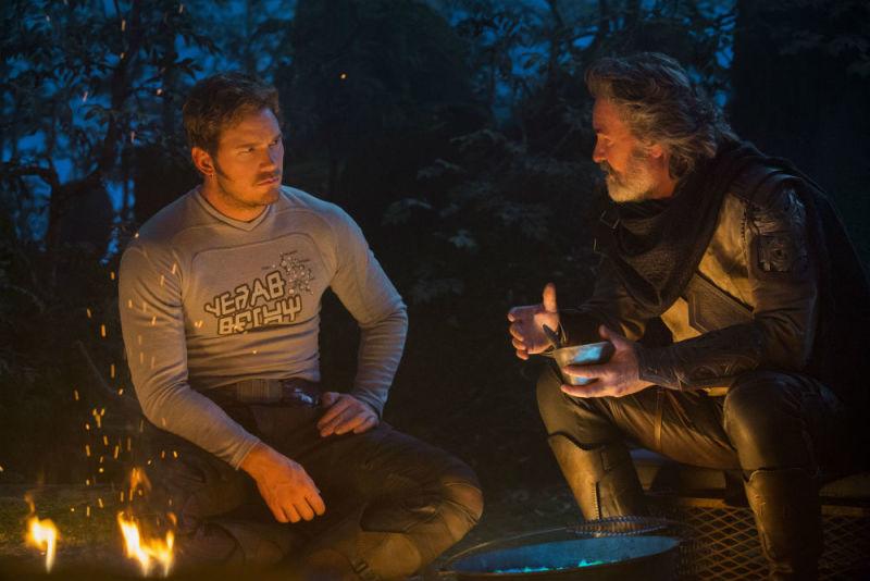 Chris Pratt and Kurt Russell sitting around a campfire and talking