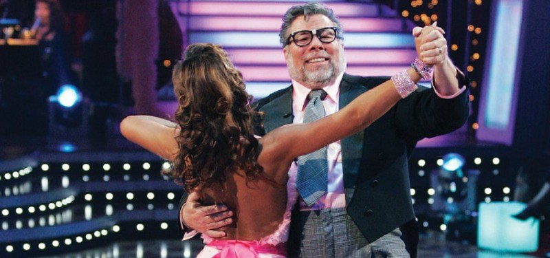 Steve Wozniak is wearing a suit and wearing glasses as he is dancing with his partner.