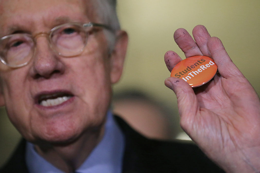 Harry Reid holds up a campaign button for the #InTheRed campaign to tackle student debt
