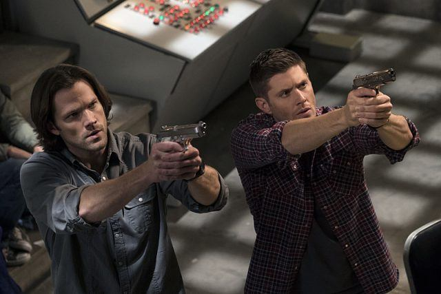 Sam and Dean aiming guns at an enemy.