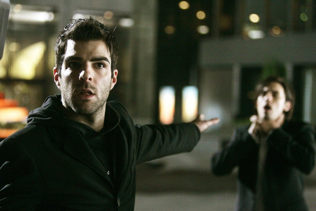 Zachary Quinto as Sylar, holding his left arm out, and telepathically choking his foe while looking into the camera