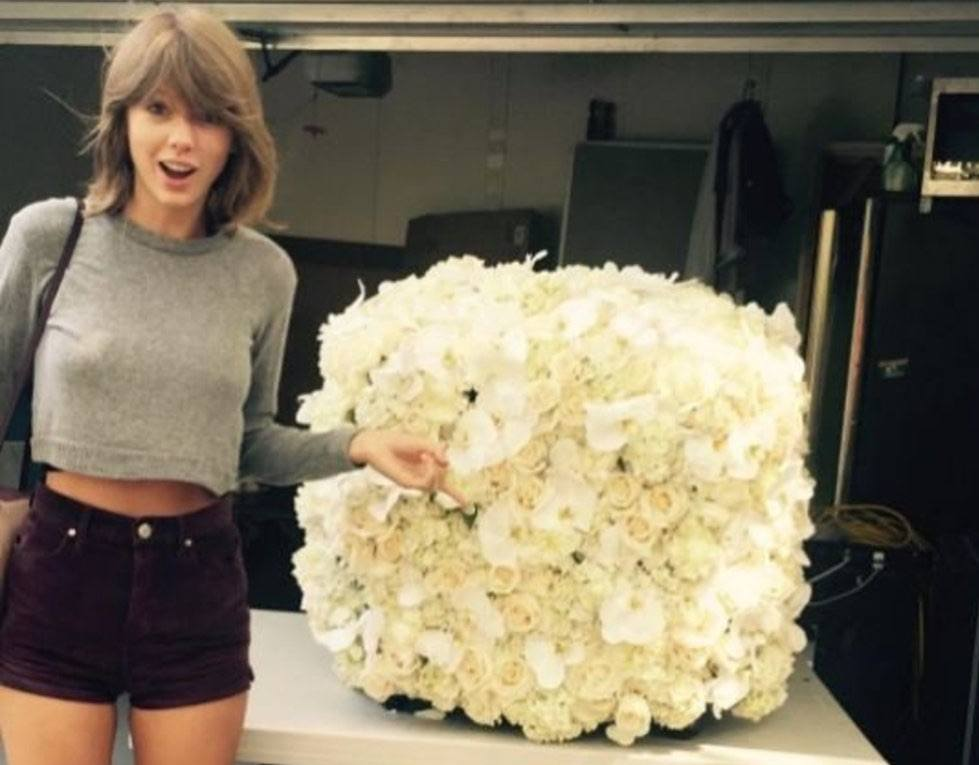 Taylor Swift points to a cube of white flowers