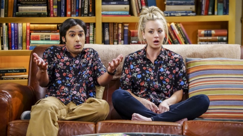 Raj and Penny sit next to each other on the couch in matching floral shirts in The Big Bang Theory