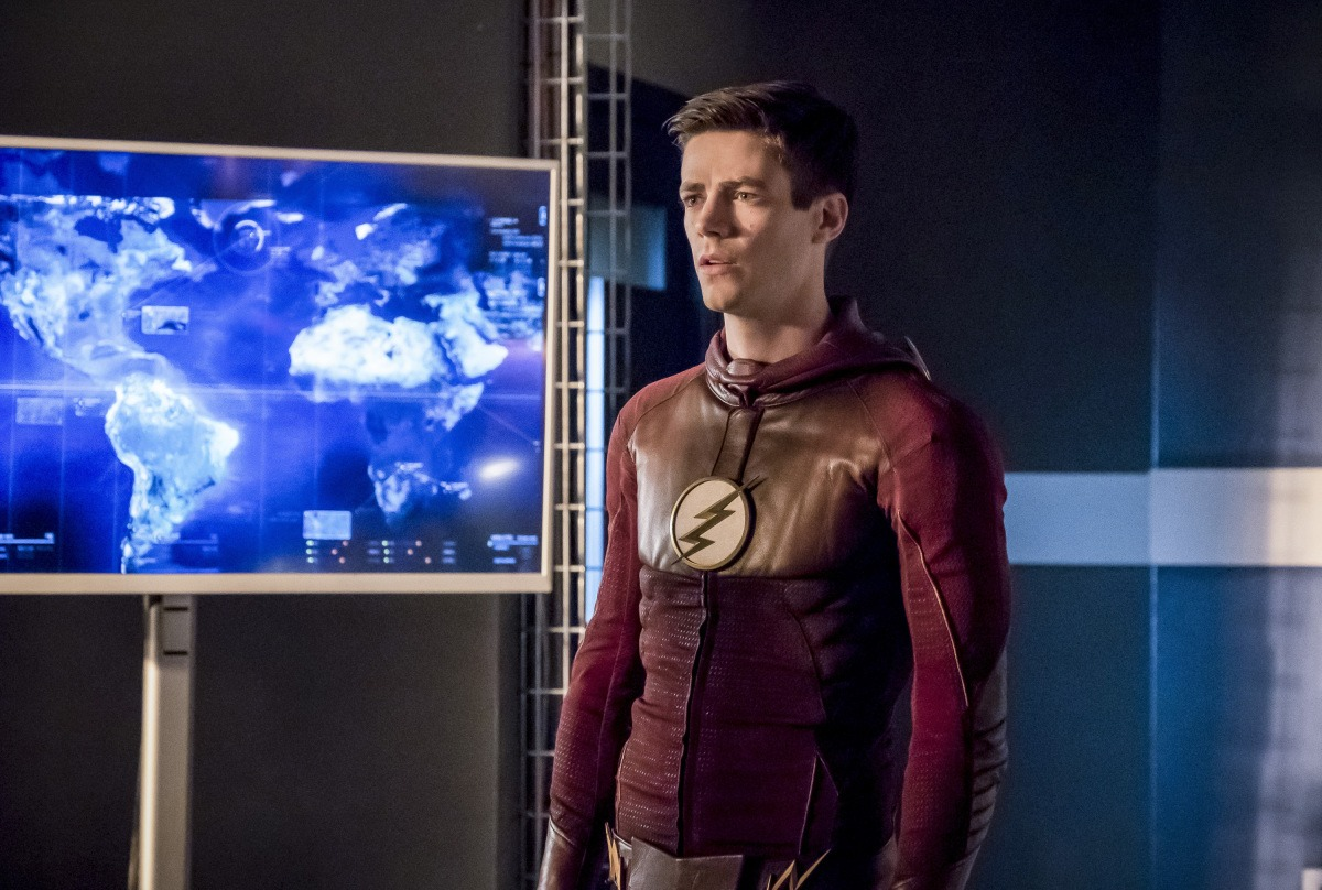 Grant Gustin wears his Flash costume in front of a blue map of the world in The Flash Season 3 finale