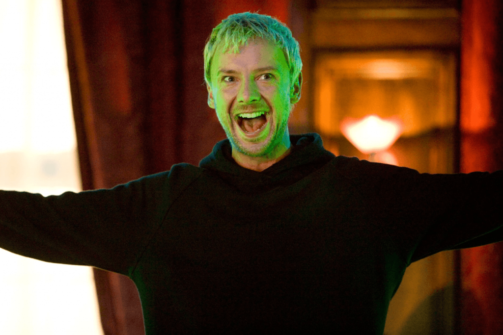 The Master wearing a bagging black sweatshirt, smiling and spreading his arms out wide