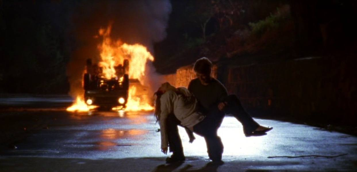 Ryan lifting Marissa off the ground while a car burns in the background