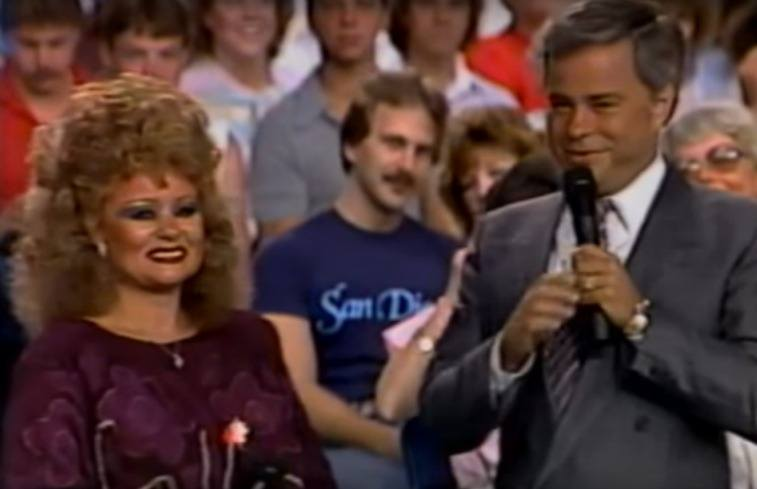 Tammy Faye stands with husband Jim Bakker who's holding a microphone in front of a studio audience