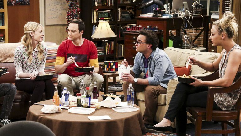 Ramona sits next to Sheldon on a couch and talks to Leonard and Penny in The Big Bang Theory