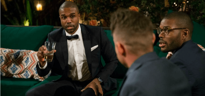 DeMario is talking to two other men and they are all wearing suits.