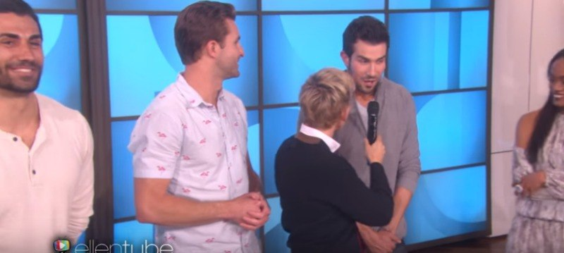 Brian is talking into a microphone that Ellen DeGeneres is holding.