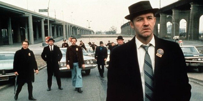 Gene Hackman is in a suit and is wearing a hat. He is standing in front of a group of men in The French Connection.