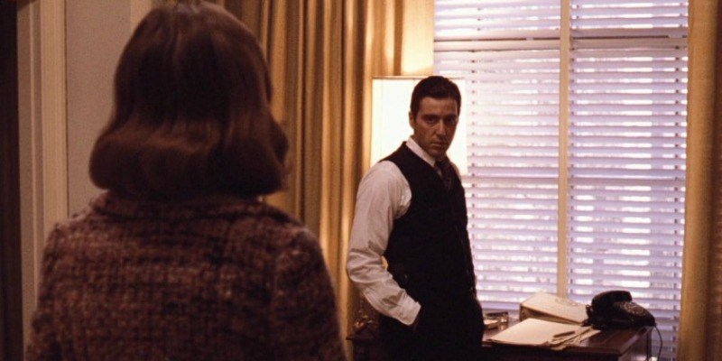Michael Corleone looks at Kay angrily while standing by a window