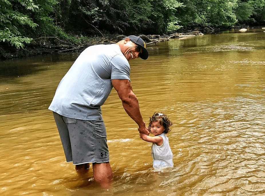 """Dwayne """"The Rock"""" Johnson holds hands with his young daughter in a lake"""