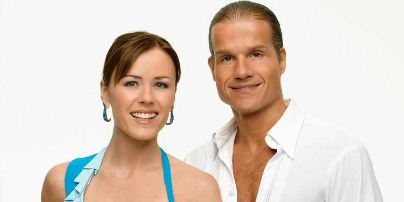 Trista Sutter and Louis Van Amstel are smiling next to each other.