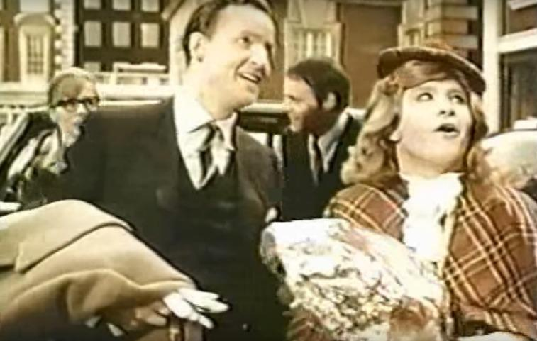 A man in a suit speaking with a man dressed in drag