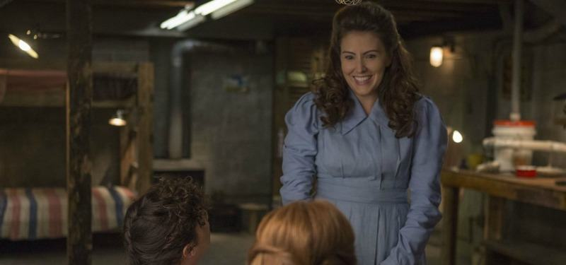 Gretchen is in a blue dress and is talking to the other girls in the bunker.