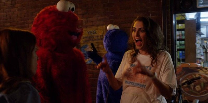 Gretchen has messed up hair and is wearing a t-shirt will standing next to Elmo on the street.