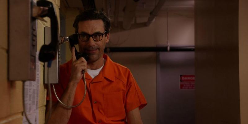 Jon Hamm is in an orange jumpsuit and is talking at a payphone in prison.