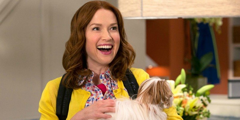 Kimmy is in a yellow jacket and is holding a dog.