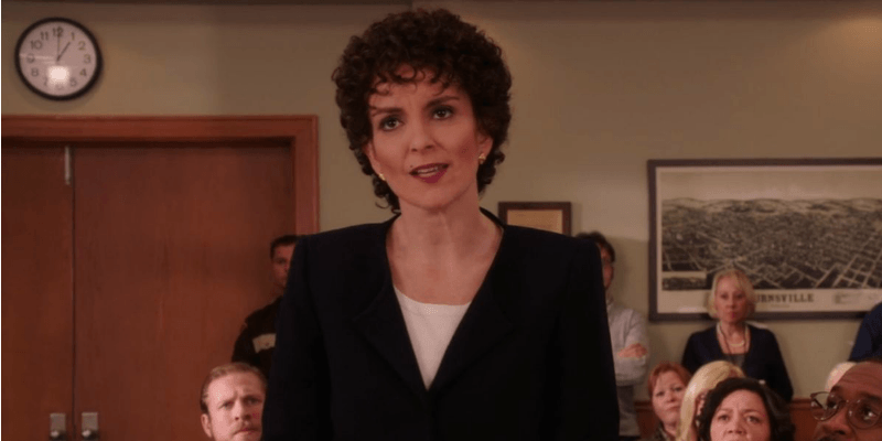Tina Fey has a short and curly hair cut and is acting as a lawyer in a court room.