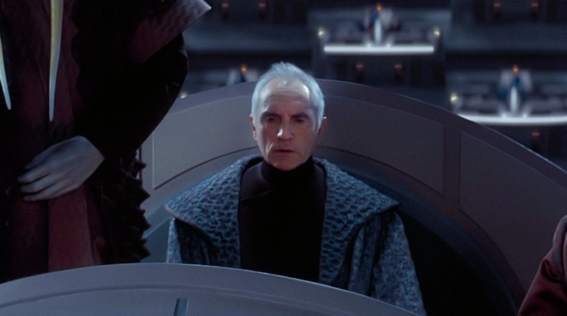 Chancellor Valorum wearing blue robes, looking off into the distance and sitting down