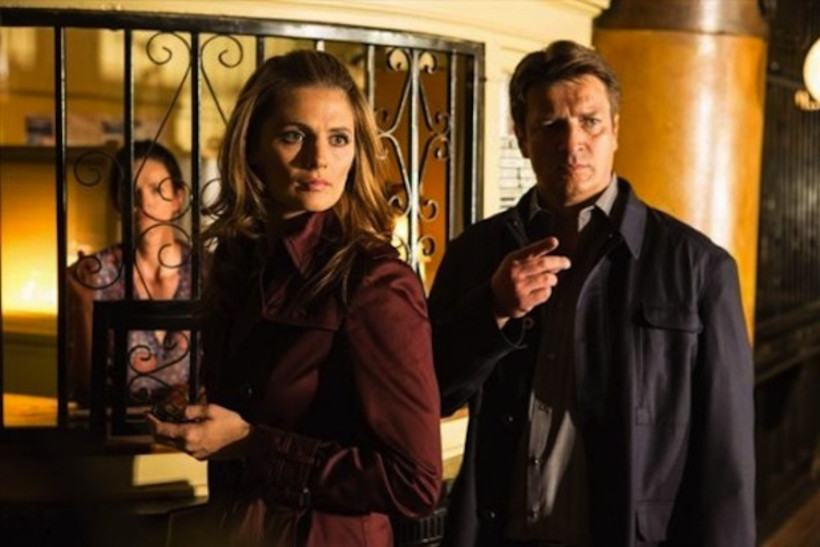 Stana Kanic and Nathan Fillion stand next to each other in a scene from Castle