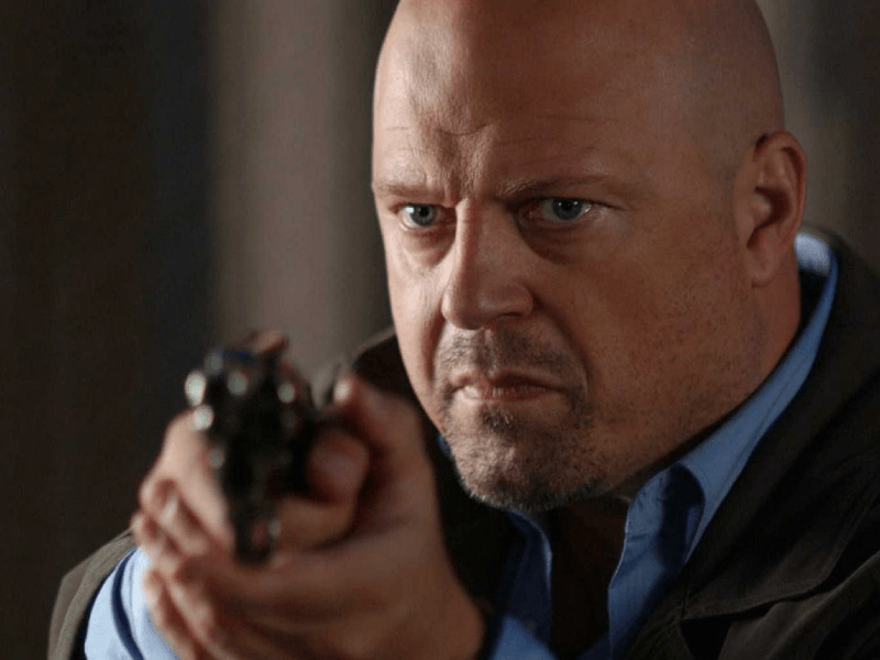 Michael Chiklis as Vic Mackey, wearing a leather jacket and pointing his gun